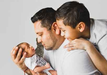 photo of man carrying newborn baby