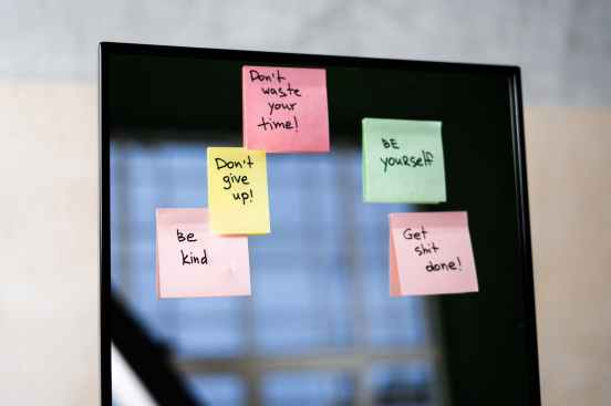 pink sticky notes on glass mirror