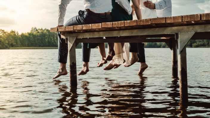 people sitting on brown wooden dock